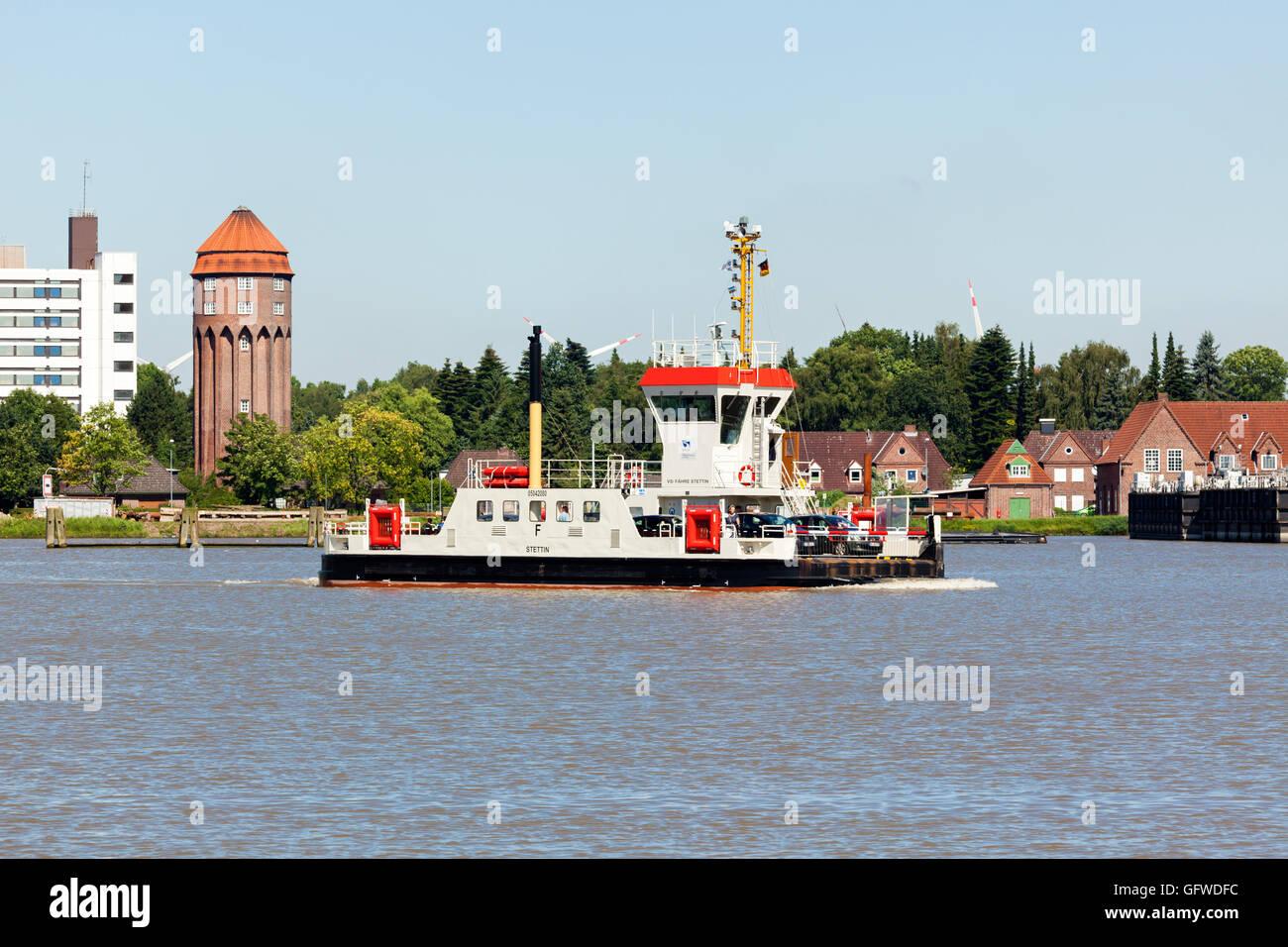 Car ferry crossing Kiel Canal at Brunsbüttel, historic water reservoir tower in background - Stock Image