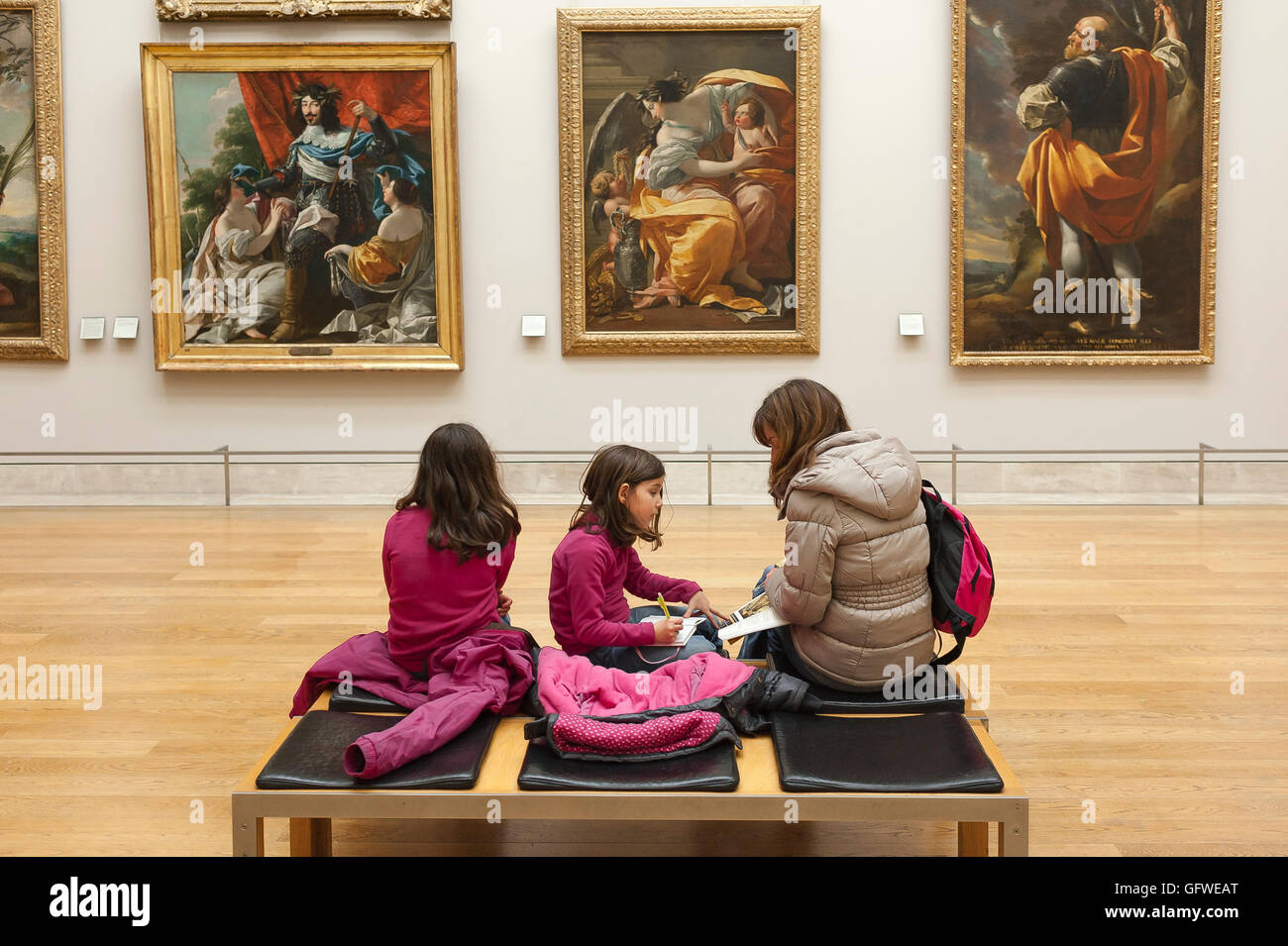 Children art gallery, a mother and her two daughters view 17th century art paintings in the Louvre Museum in Paris, - Stock Image