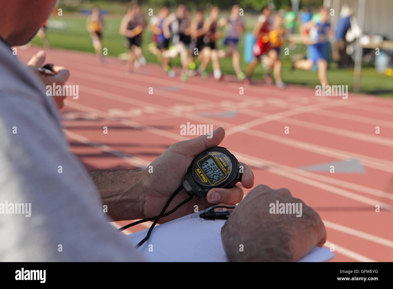 Coach at the side of a running track in White Plains, NY, USA records the lap times of high school athletes with - Stock Image