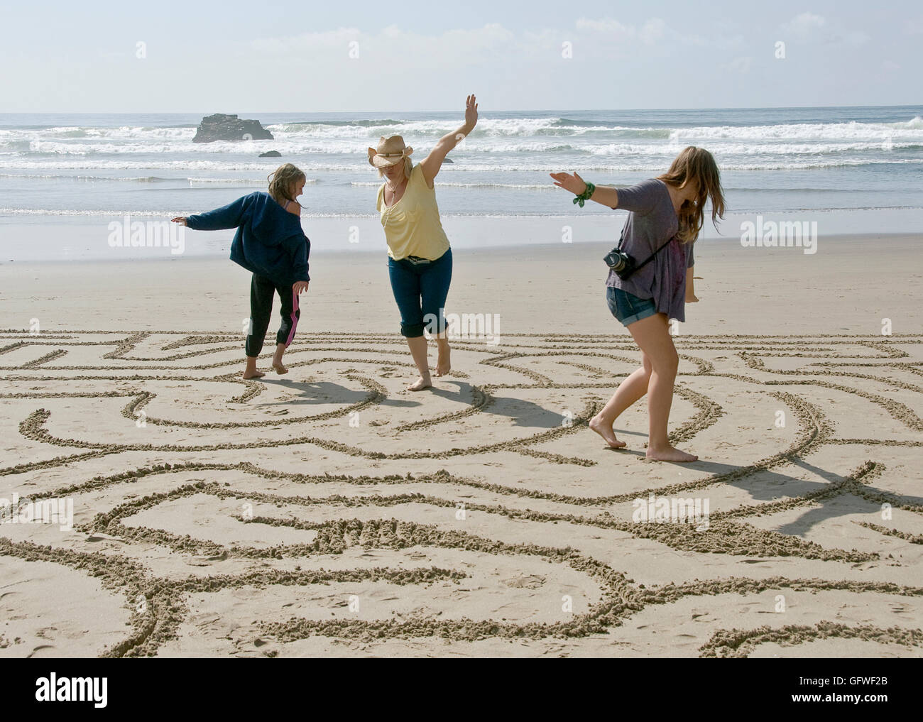 A woman and two girls going through a beach maze on an Oregon beach - Stock Image