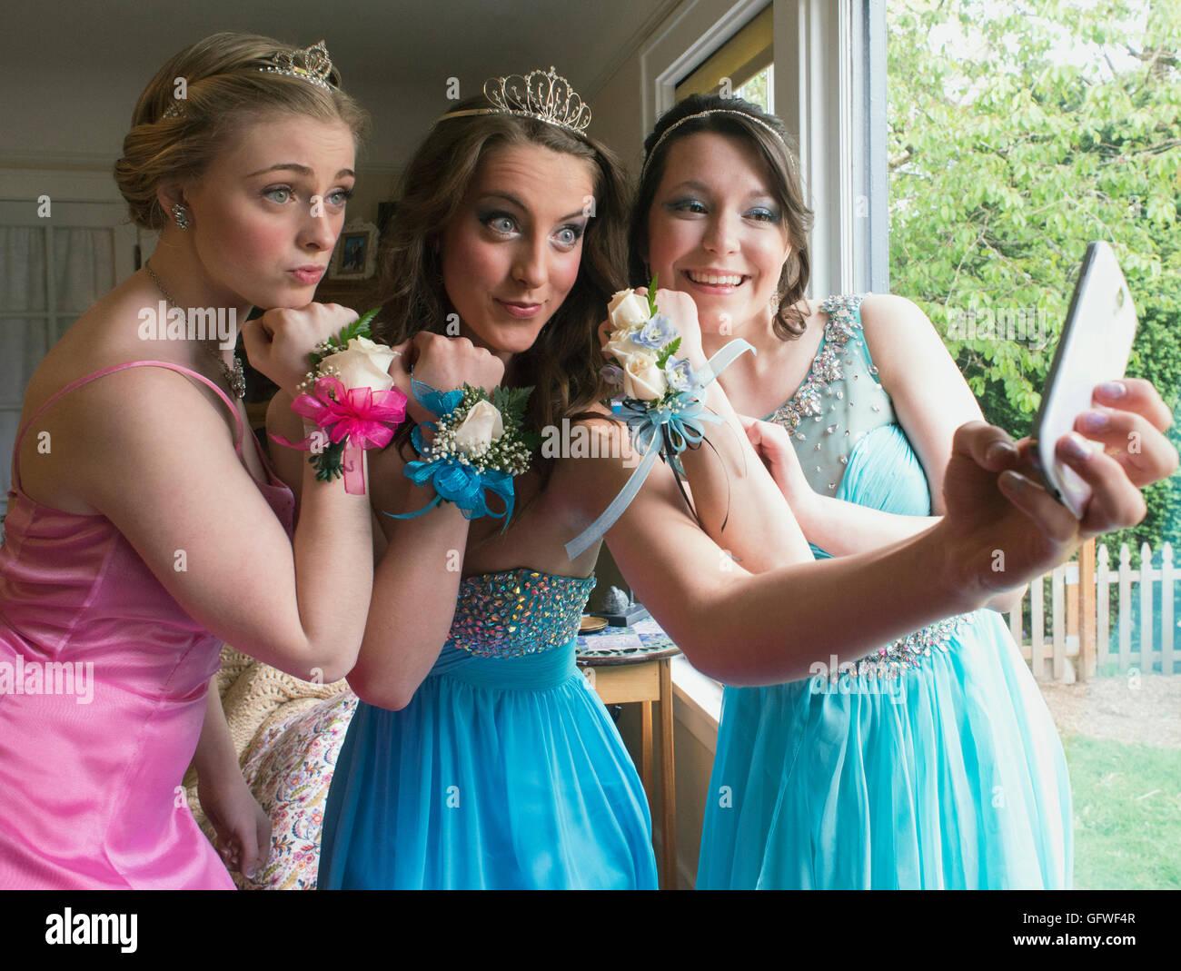 Three girls taking prom selfies. - Stock Image