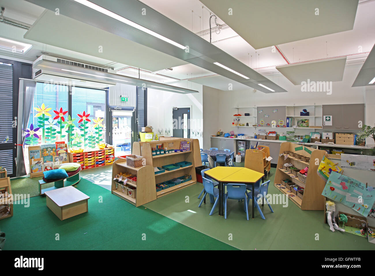 Nursery Classroom In A New London Primary School Shows Desks And Chairs With Pupils Artwork On The Walls