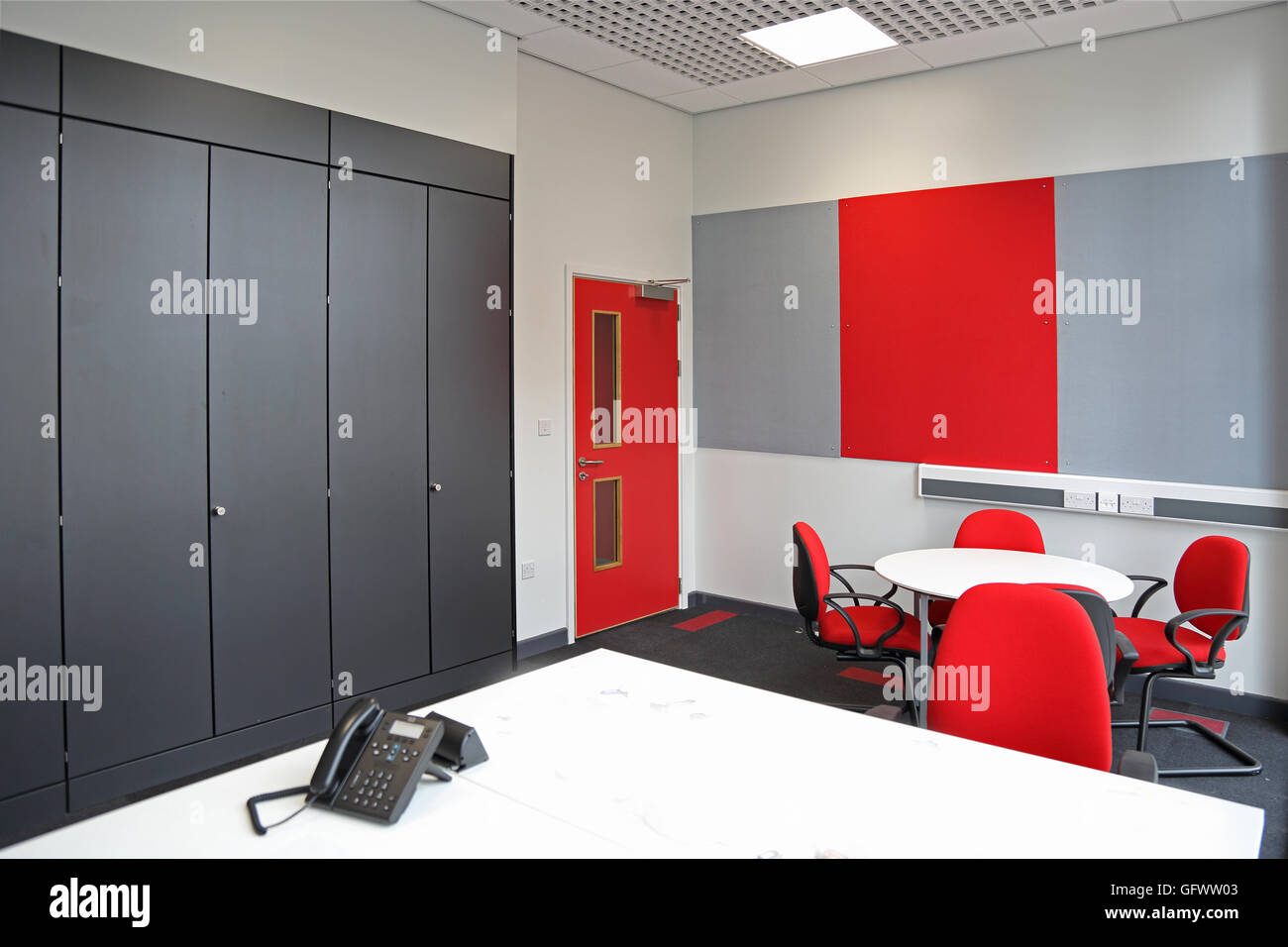Smart new office in a new London Factory. Shows desk, meeting table and starage cupboards in distinctive red and - Stock Image