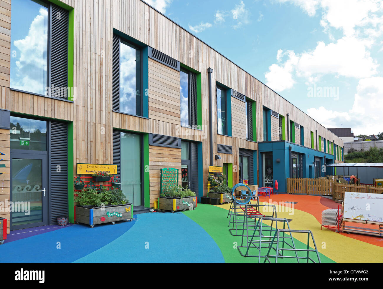 Exterior of Invicta Primary School in South London. A new timber-clad structure with  rainbow-coloured playground - Stock Image