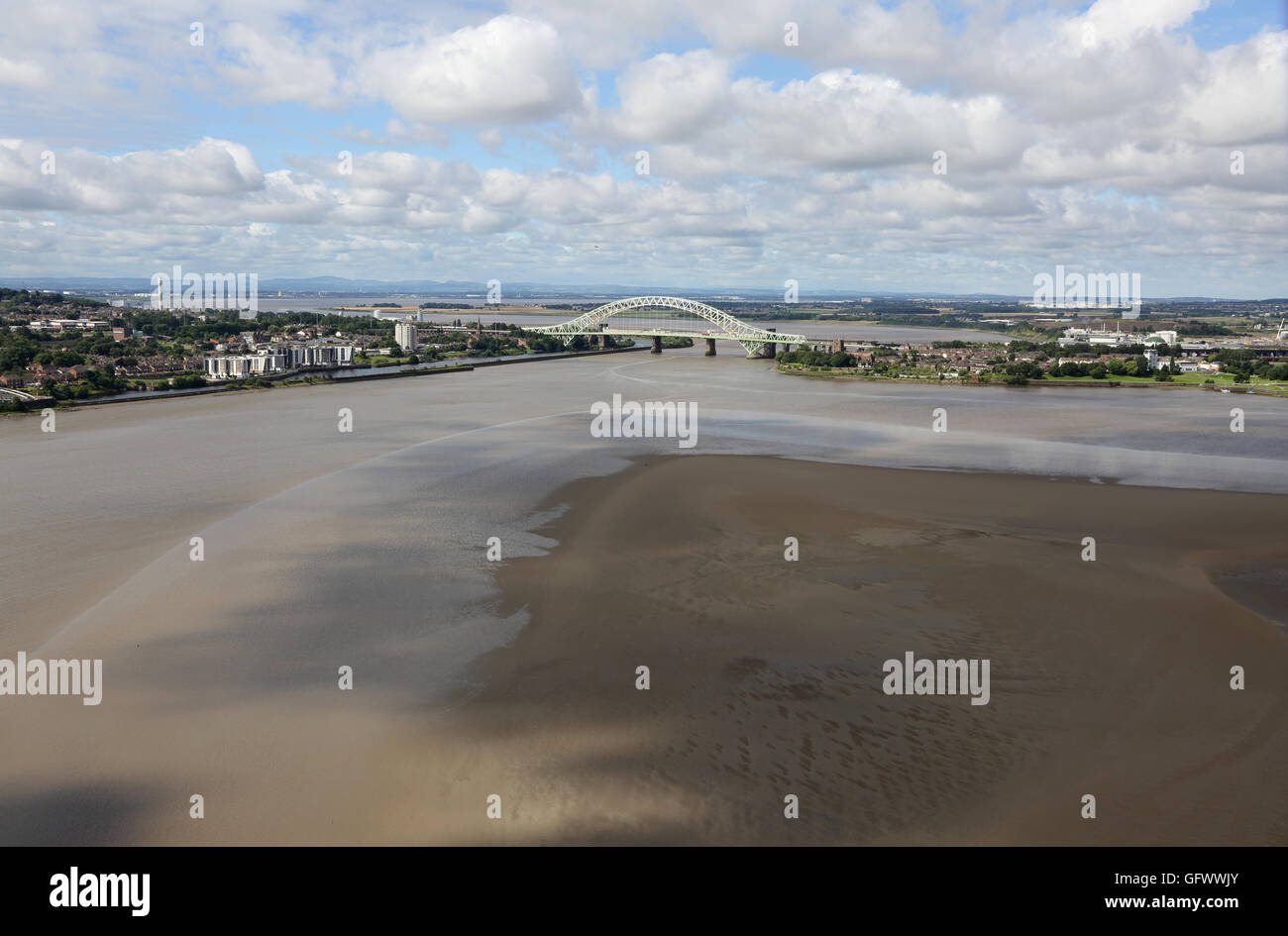 High-level view of the River Mersey at Runcorn showing the Silver Jubilee bridge, estuary mudflats and Welsh Mountains - Stock Image