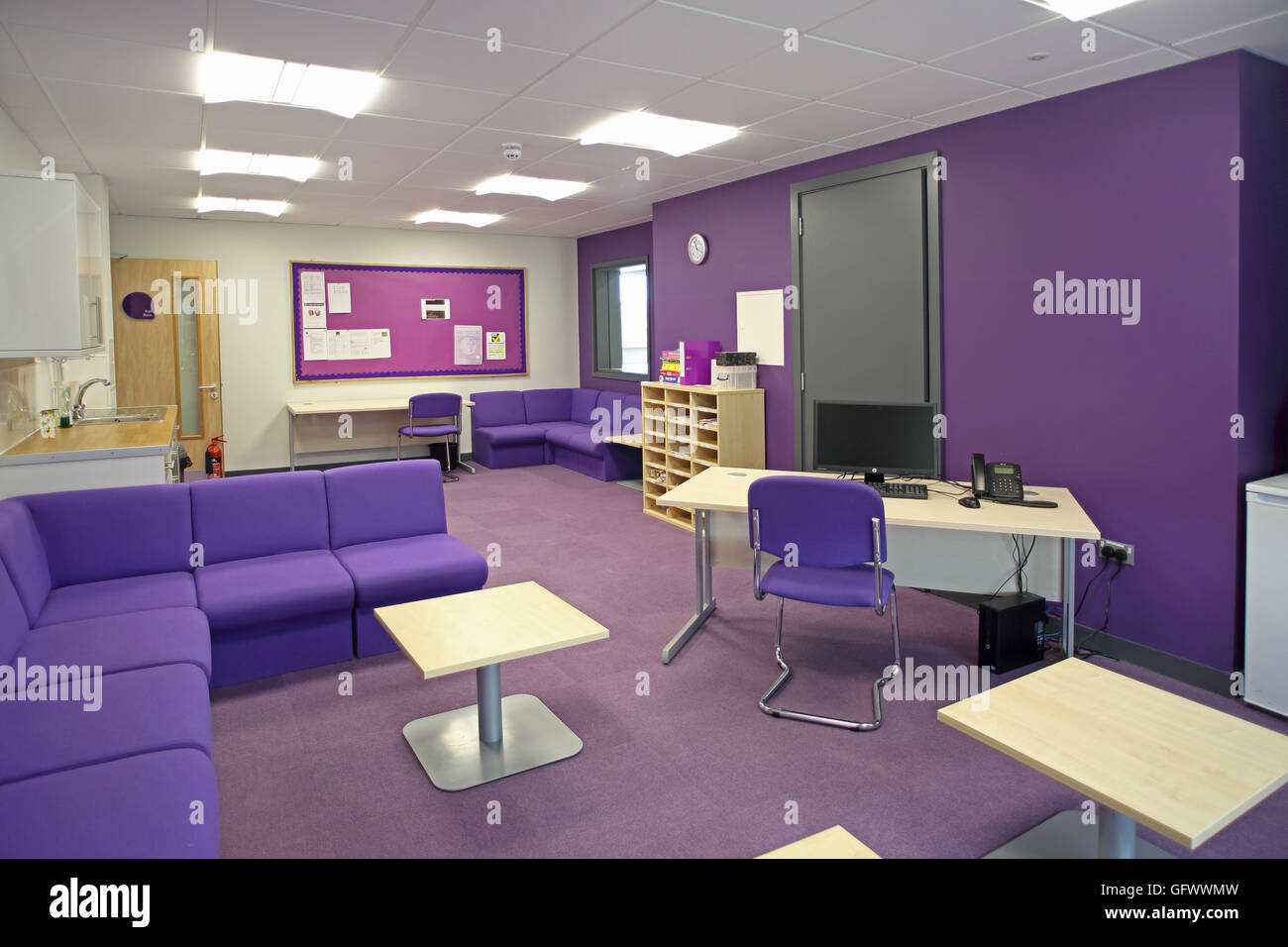 Staff administration and office area in a brand new London primary school. Shows desk and waiting area. Purple colour - Stock Image