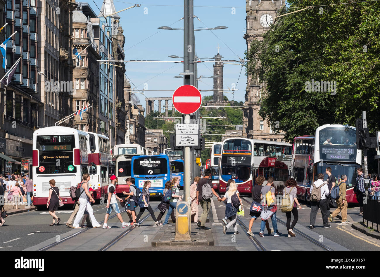 View of pedestrians crossing street and many pubic buses on Princes Street in Edinburgh , Scotland, United Kingdom - Stock Image