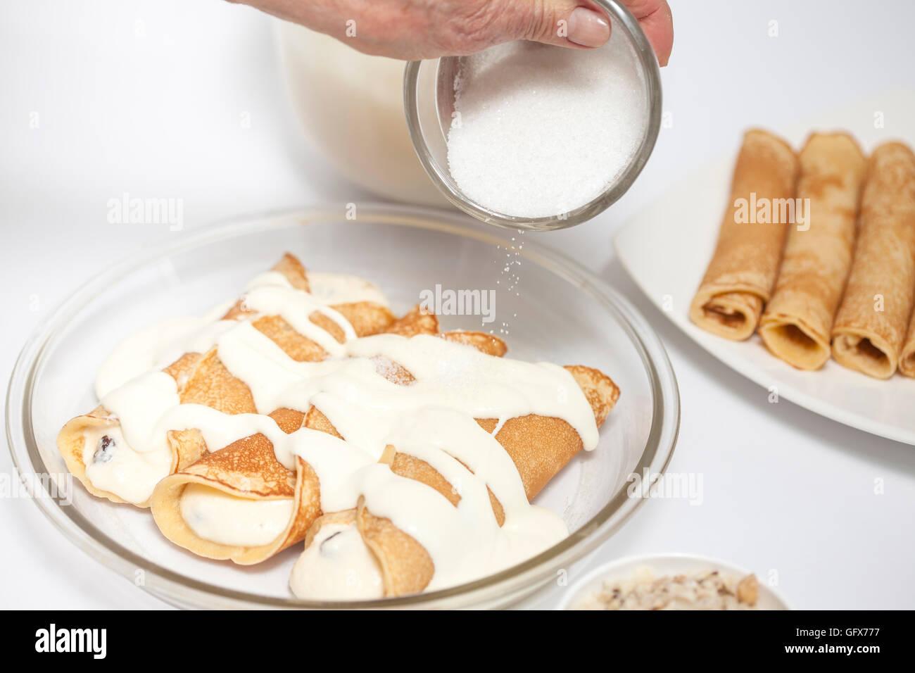 Sprinkling sugar over the topfen füllen crepes - Stock Image