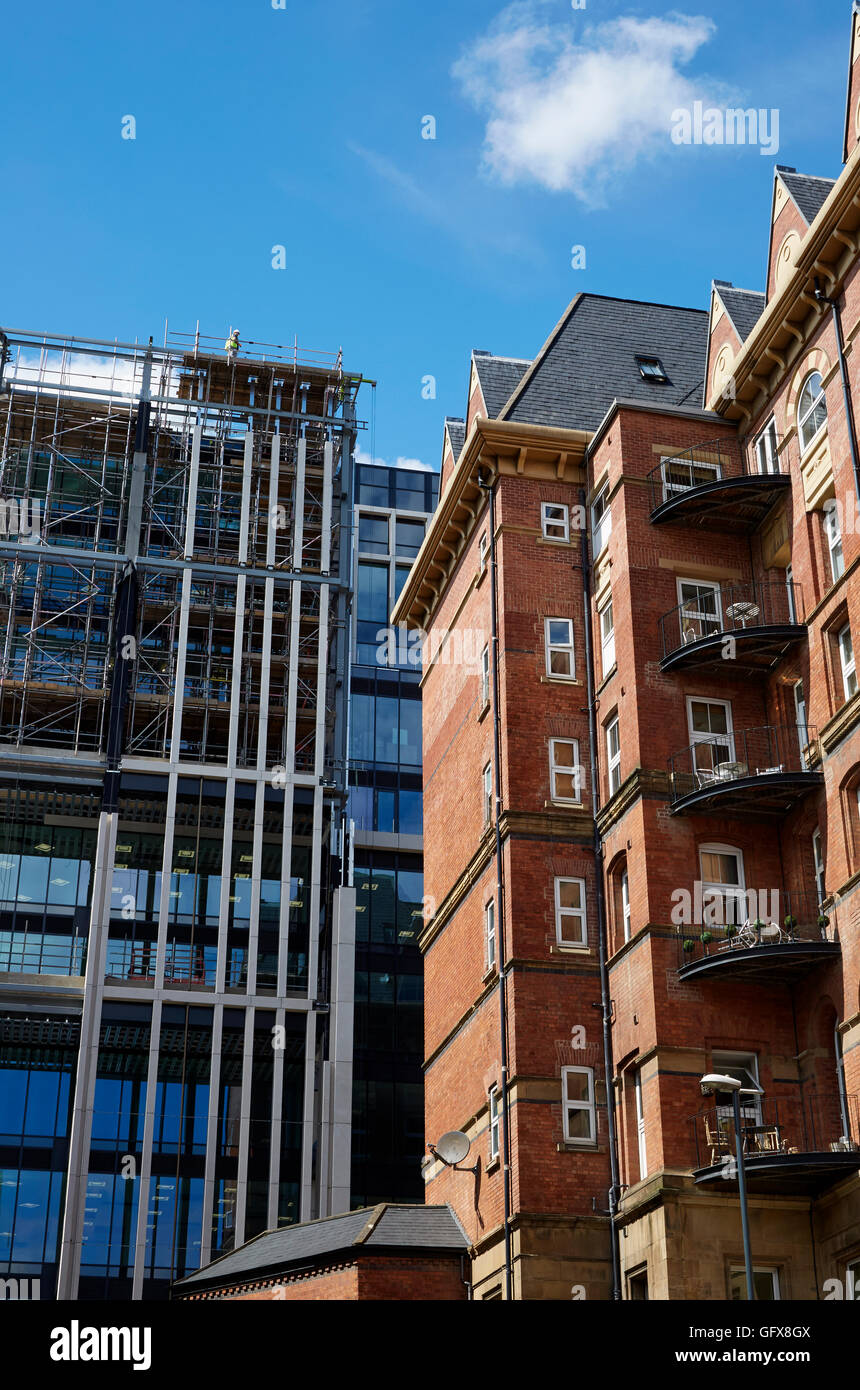 Brickwork of old building contrasted with modern building of Central Square, Leeds - Stock Image