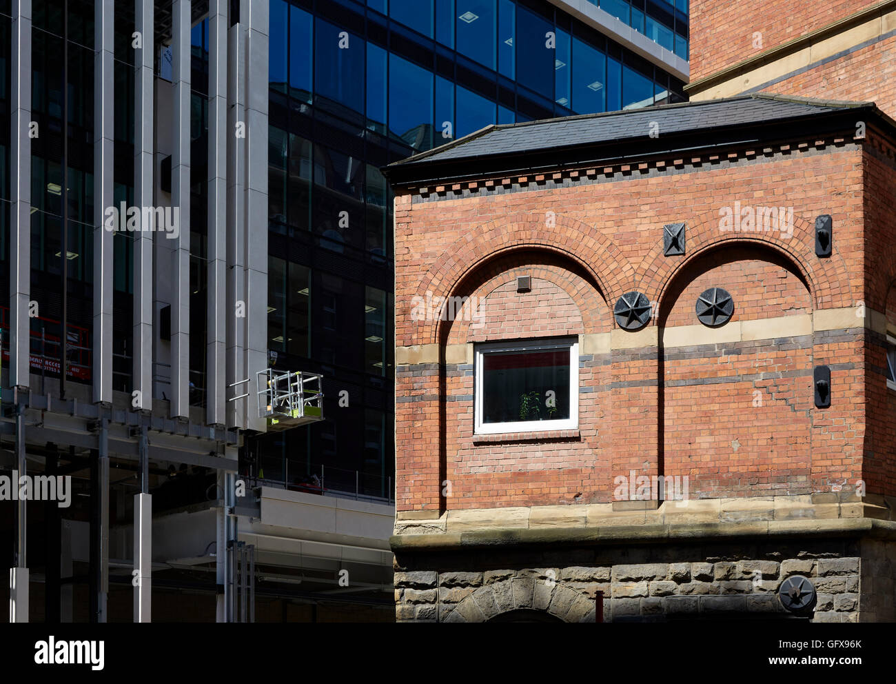 arched brickwork of old building contrasted with modern building of Central Square, Leeds - Stock Image
