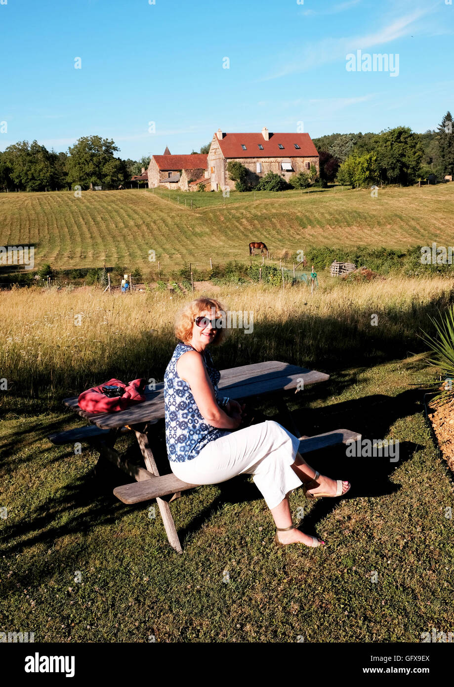 Woman on holiday enjoys late afternoon sun at gite  in Le Lot Region department South West France Midi Pyrenees Stock Photo