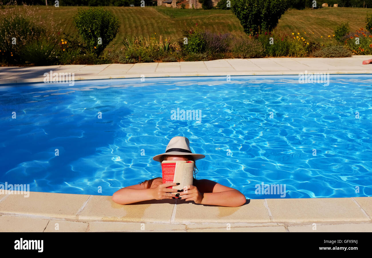 Young Woman Reading Book In Swimming Pool Holiday Gite In Le Lot Region South  West France Midi Pyrenees July 2016