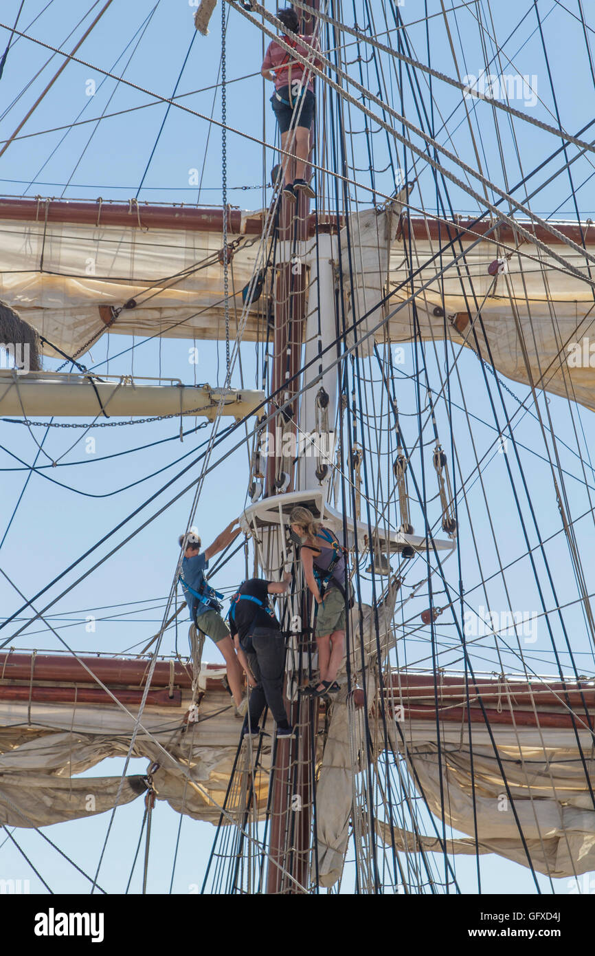 Three crew working to prepare to sail a square rigged ship at Lisbon dock during the Tall Ships Race 2016, Lisbon - Stock Image