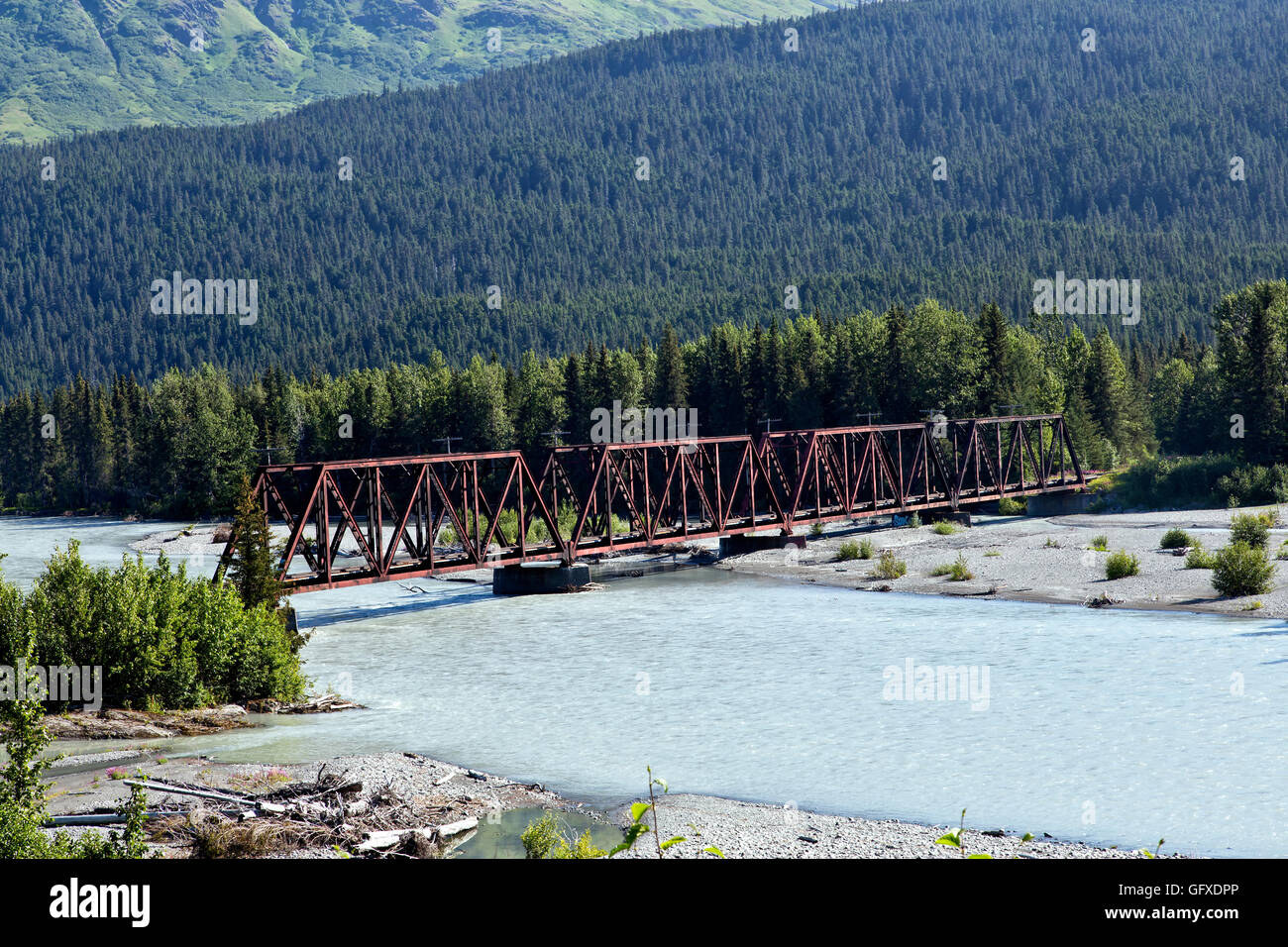 Classic Railroad trestle crossing glacier-fed Snow river. - Stock Image