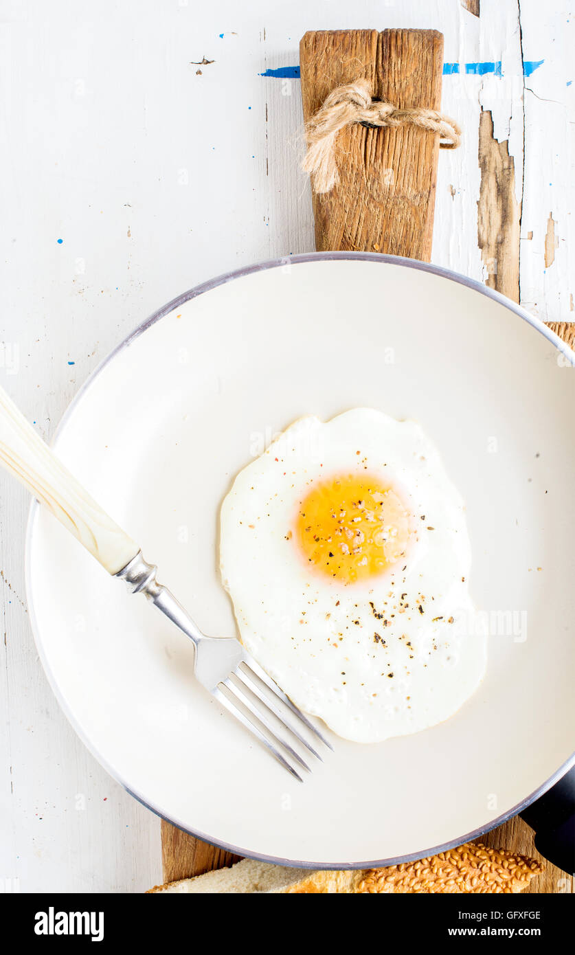 Fried egg with spice and bread slices in white ceramic frying pan on wooden board - Stock Image