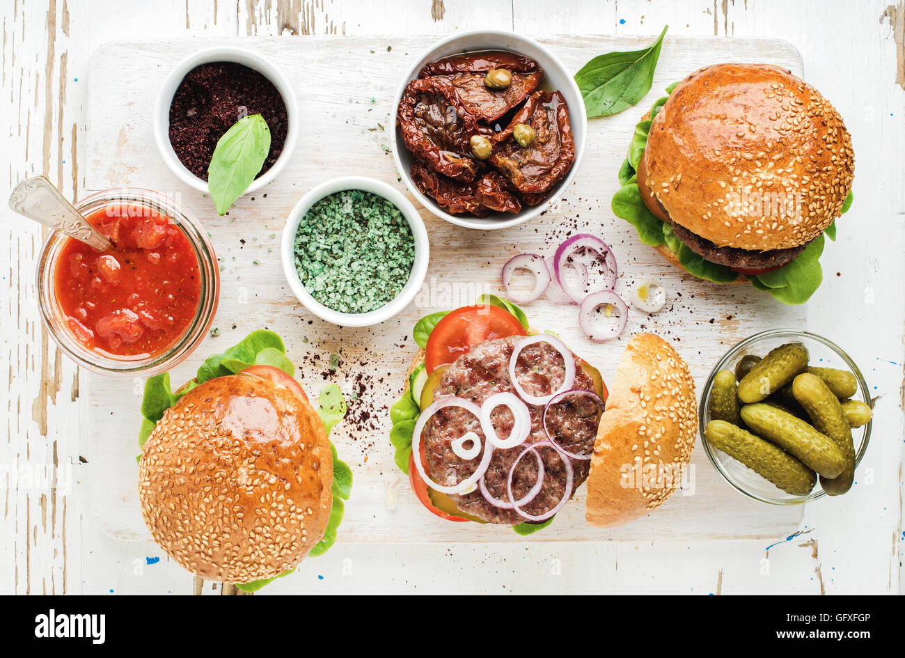 Homemade beef burgers with onion, pickles, vegetables, sun-dried tomatoes, sauce - Stock Image