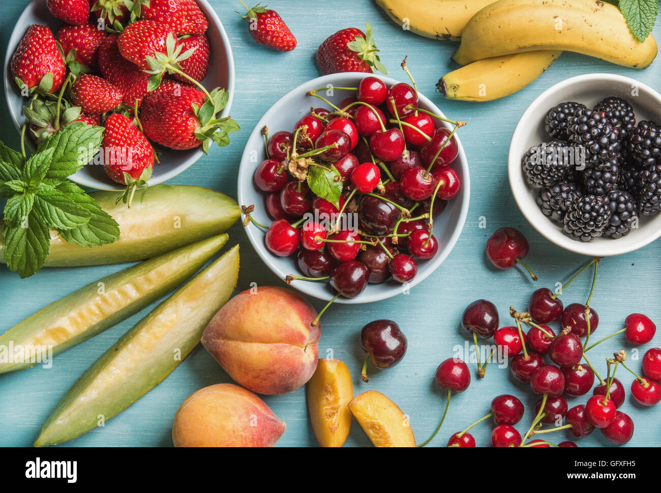 Healthy summer fruit variety on blue wooden backdrop - Stock Image