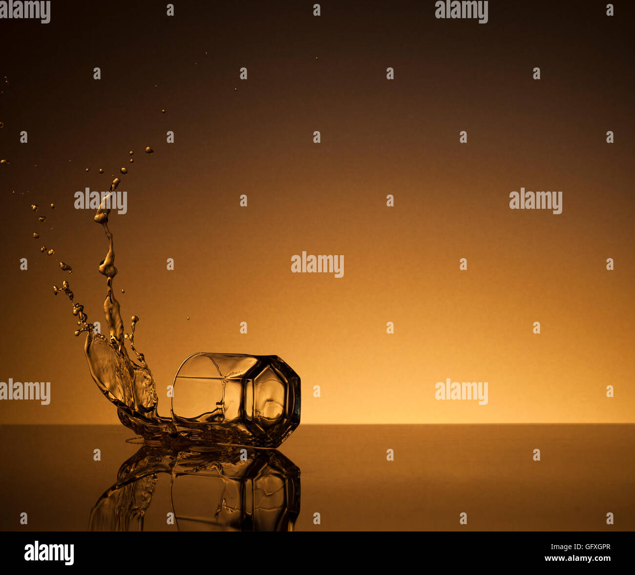 A glass of alcoholic beverage and drops on a gold background - Stock Image