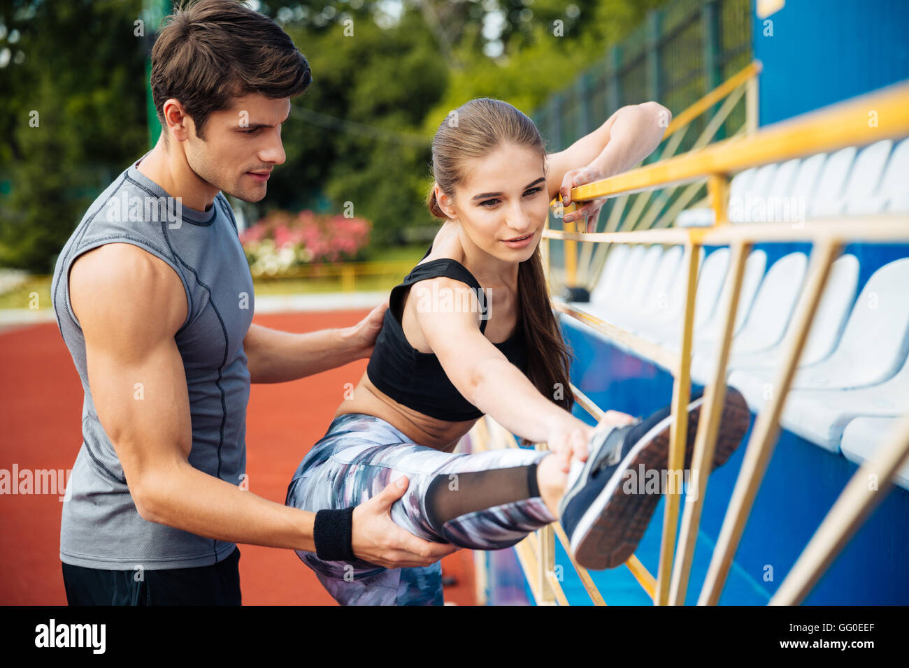 Cute young woman athlete working out with personal trainer on stadium - Stock Image