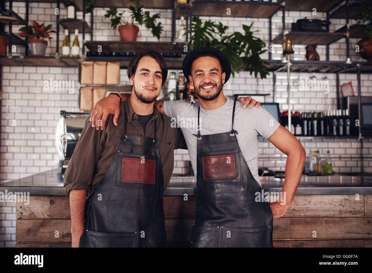 Portrait of two young coffee shop owners standing together at the bar counter and looking at camera. - Stock Image