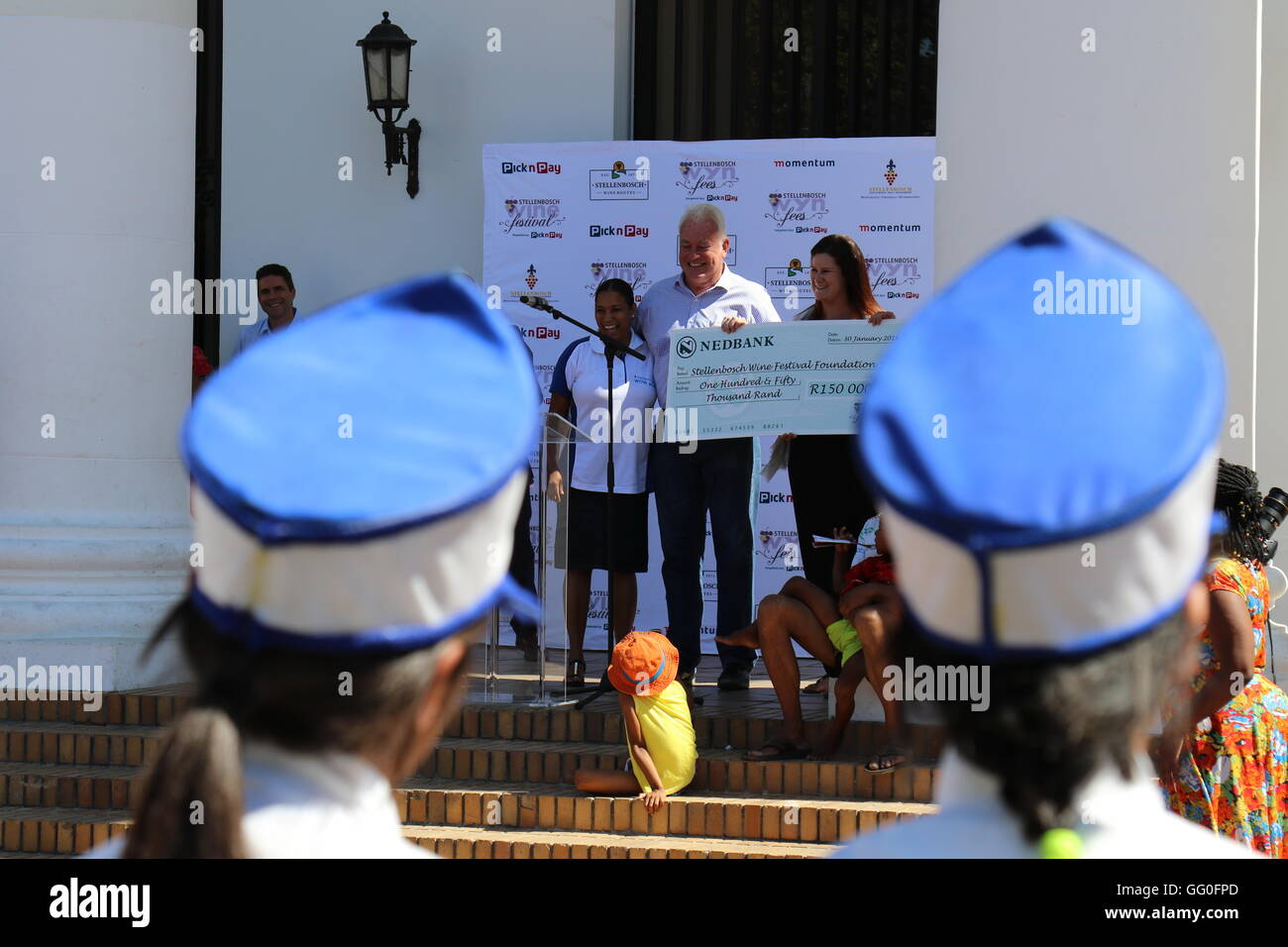 People posing and smiling at the hand over of a donated cheque at the 2016 Stellenbosch wine parade - Stock Image