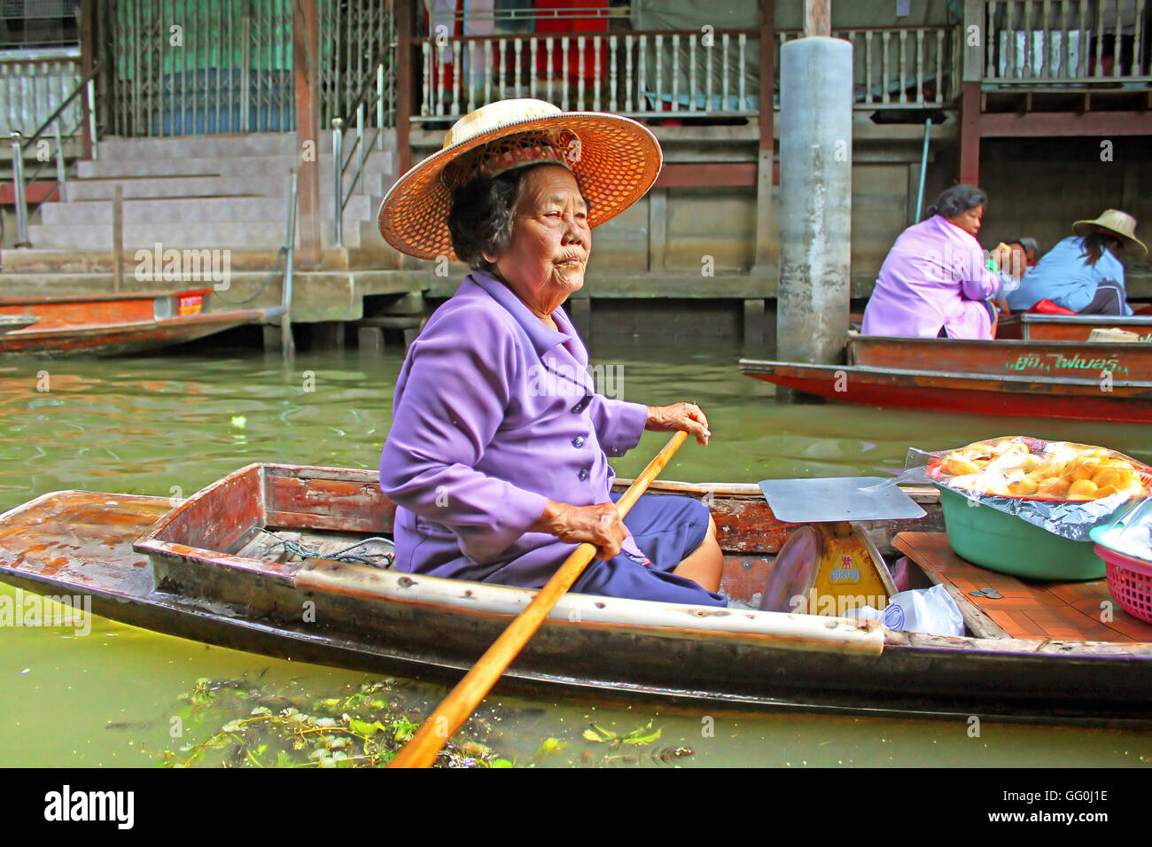 KANCHANABURI, THAILAND - JUNE 11, 2014: Unidentified woman is sails in the floating market along raft houses at - Stock Image