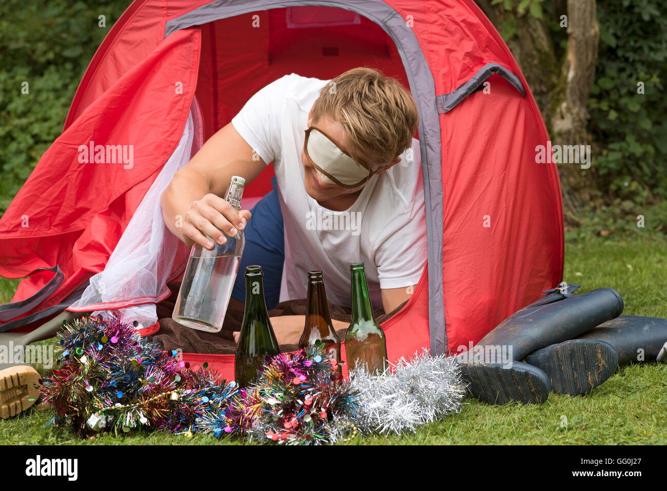 CAMPING PARTY TIME  - A young man reaches outside a tent for a water bottle - Stock Image