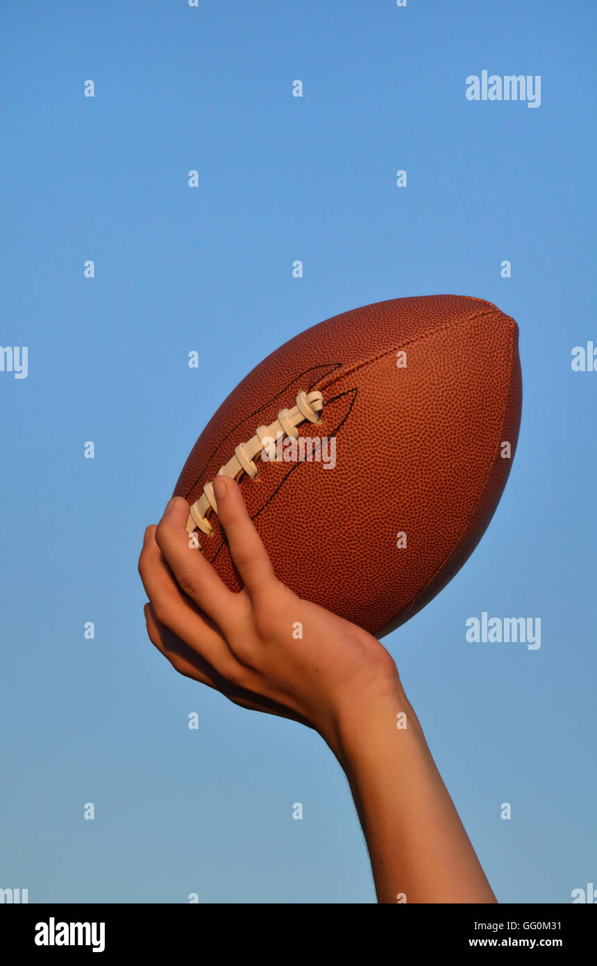 Quarterback Throwing an American Football Against a Blue Sky - Stock Image