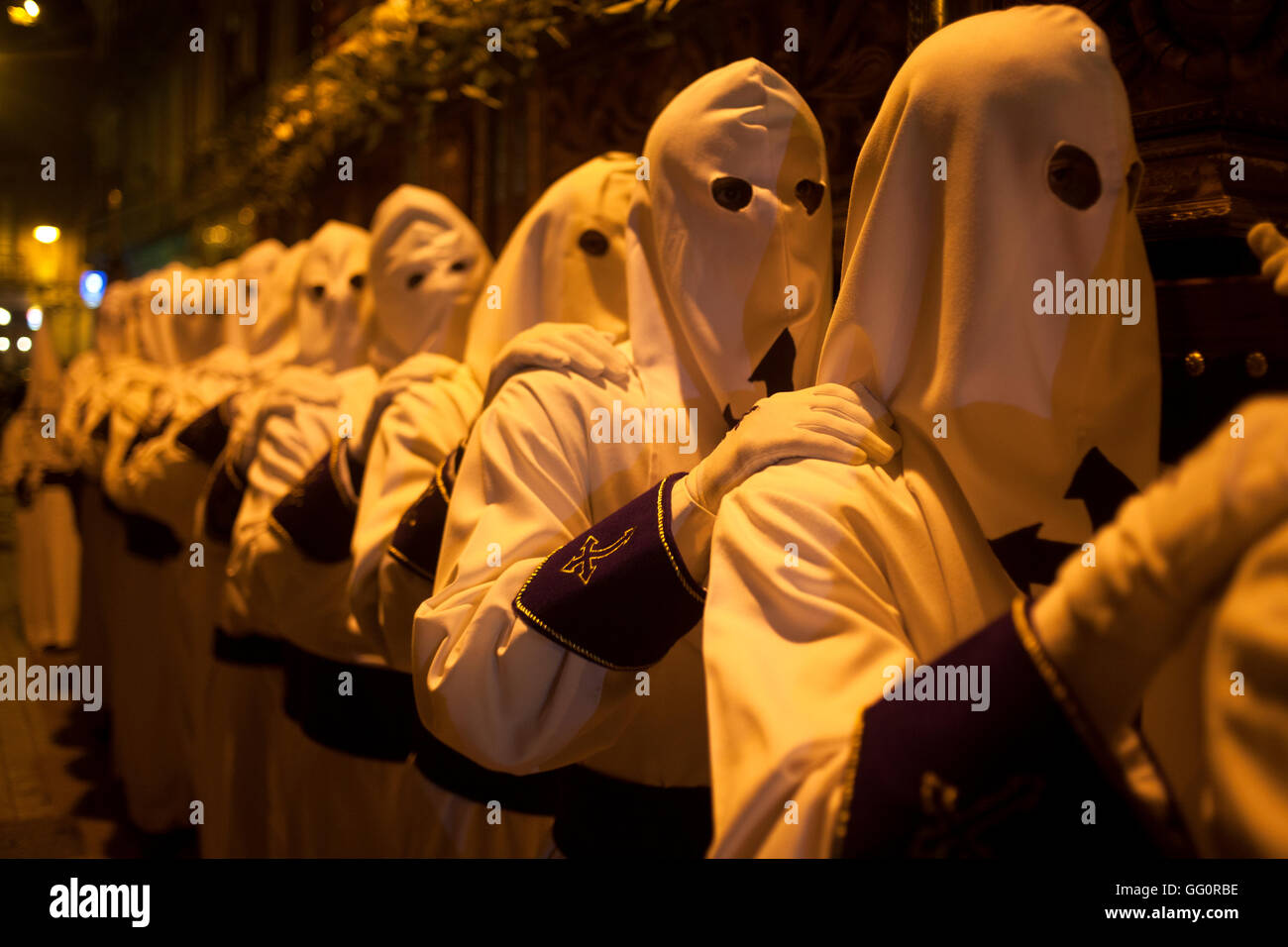 Hooded penitents hold a throne during an Easter Holy Week procession in Astorga, Castilla y Leon, Spain. - Stock Image
