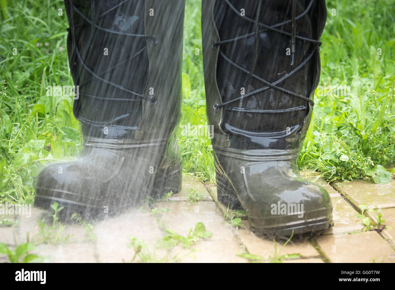 Rubber boots in the rain, close-up Stock Photo
