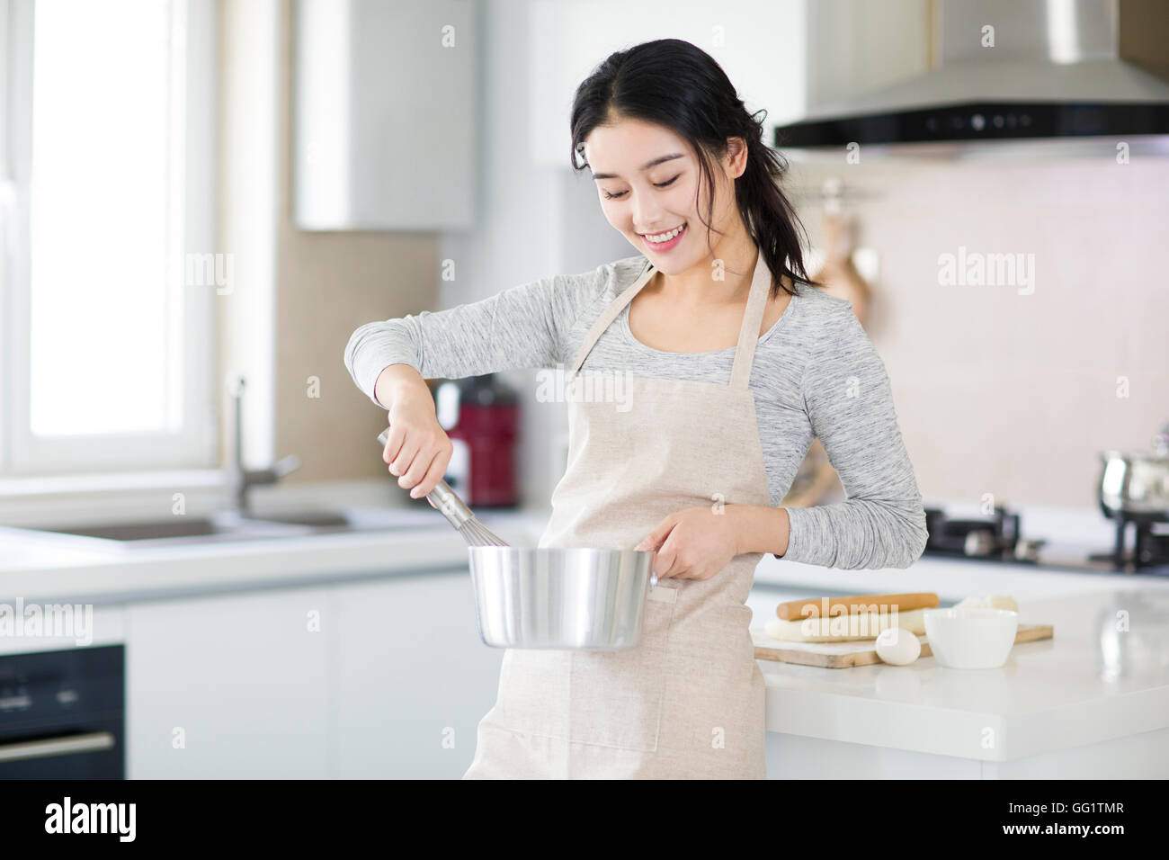 cheerful young chinese woman cooking in kitchen stock photo