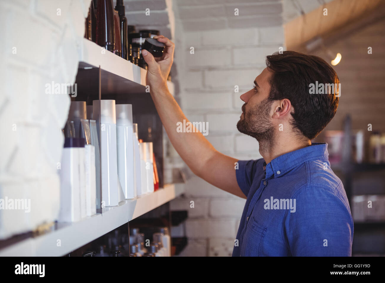 Male hair dresser selecting gel from shelf - Stock Image