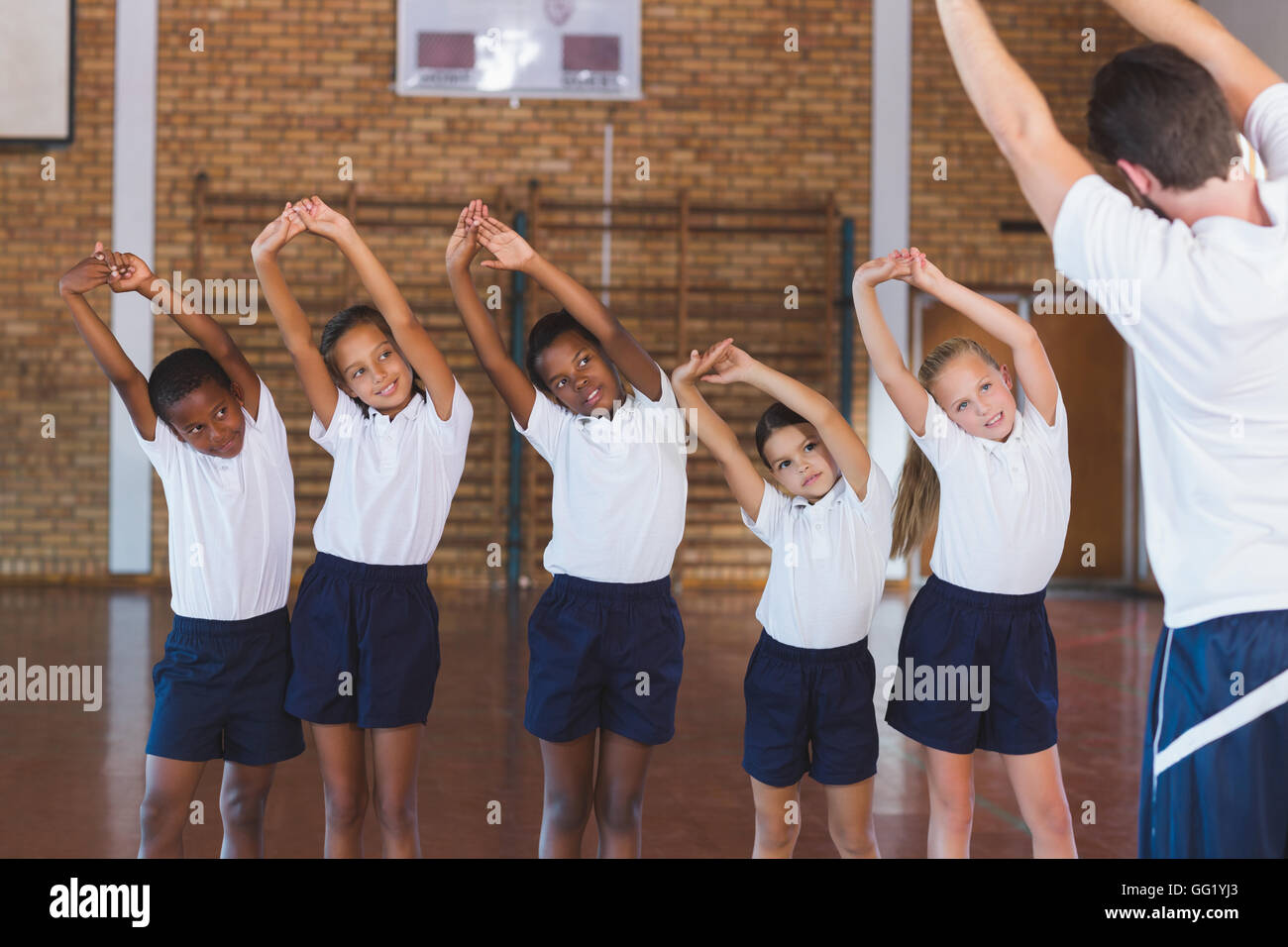 Teacher teaching exercise to school kids in basketball court - Stock Image