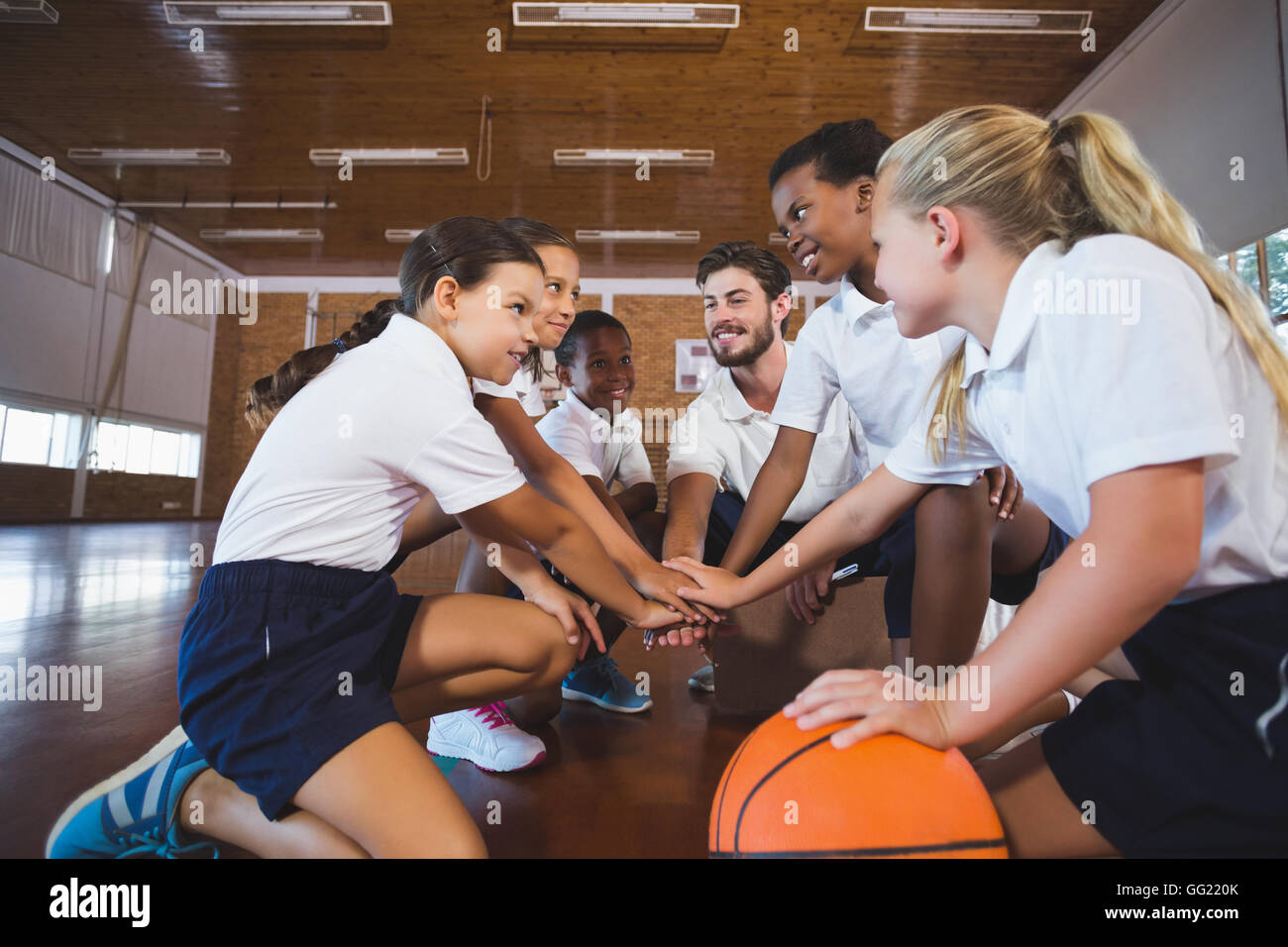 Sports teacher and school kids forming hand stack in basketball court - Stock Image