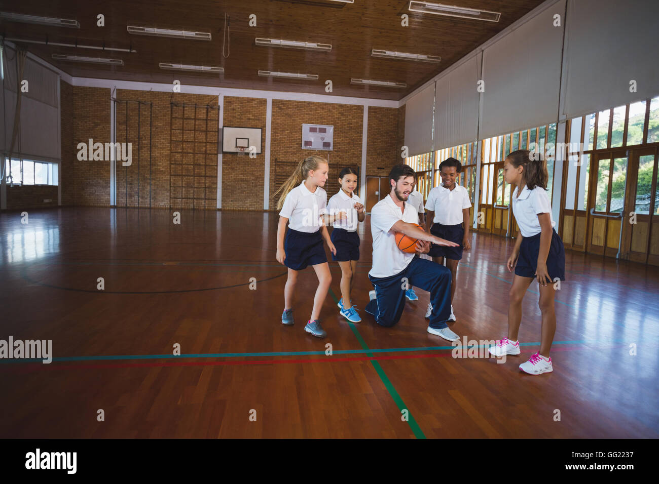 Sports teacher teaching school kids to play basketball - Stock Image