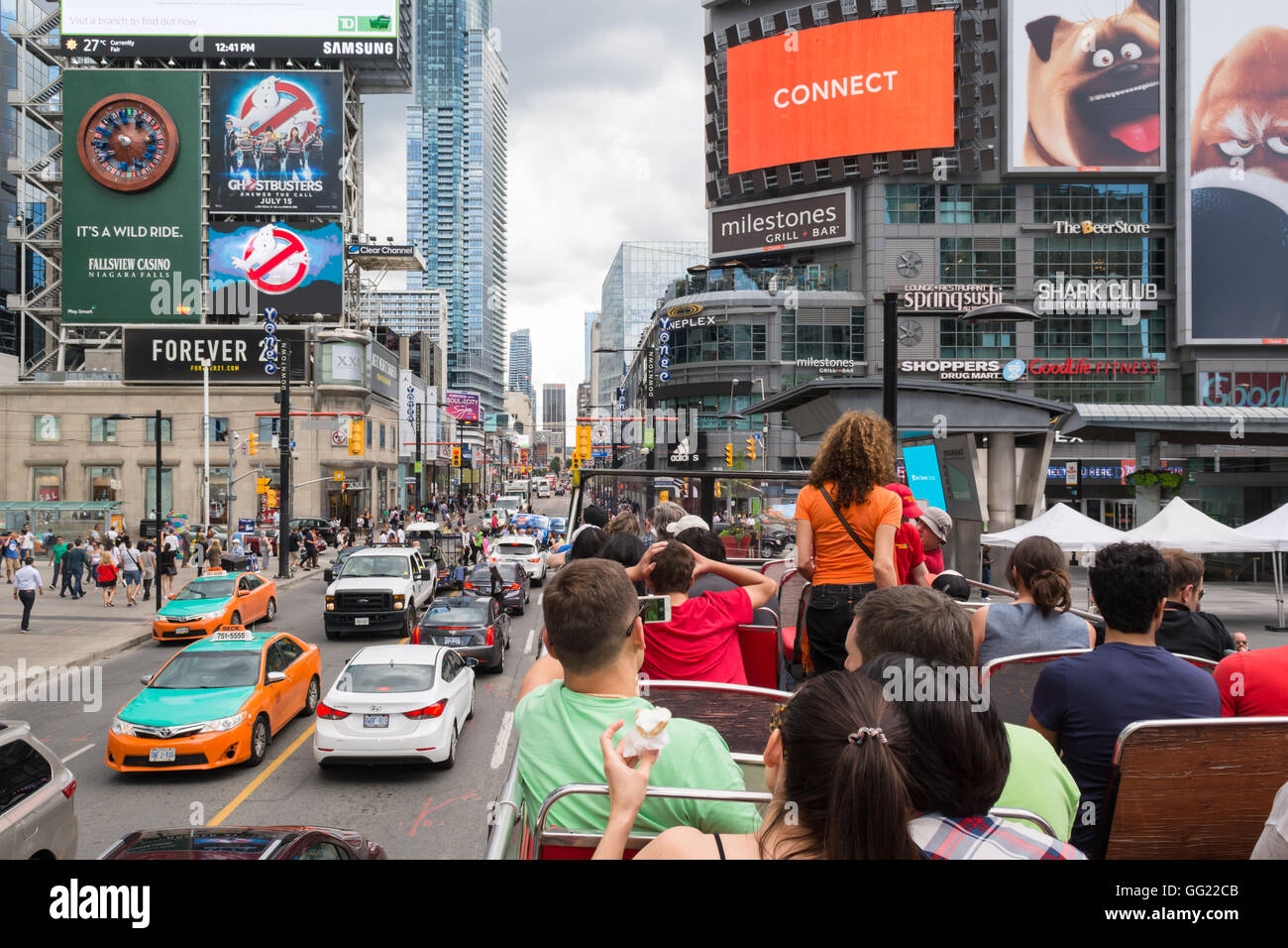 Downtown Toronto -Dundas Square - tourists on hop on hop off bus tour at Yonge-Dundas Square, Toronto, Canada - Stock Image