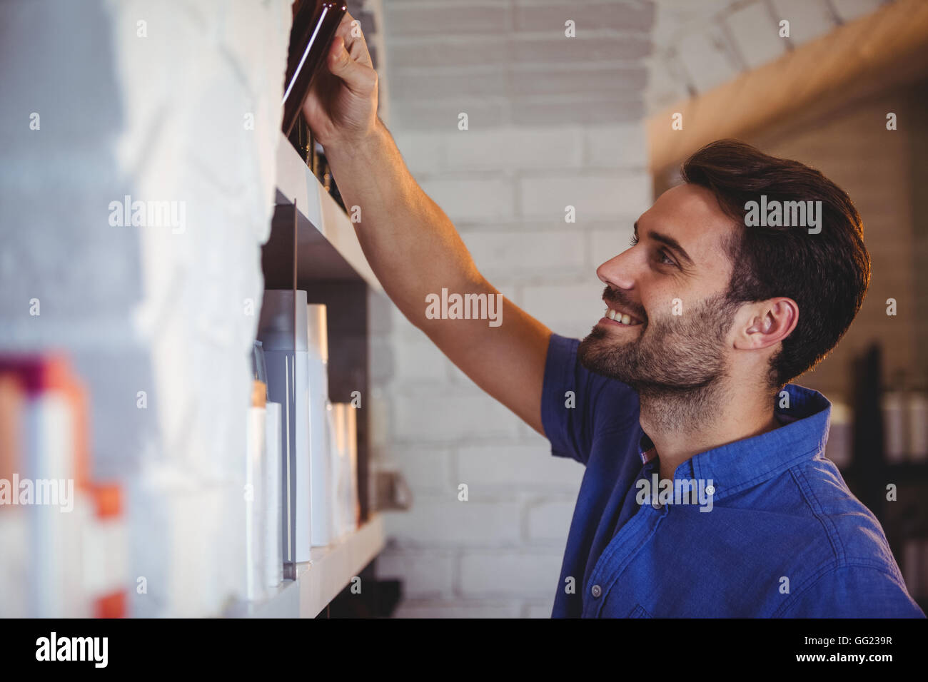 Male hair dresser selecting shampoo from shelf - Stock Image