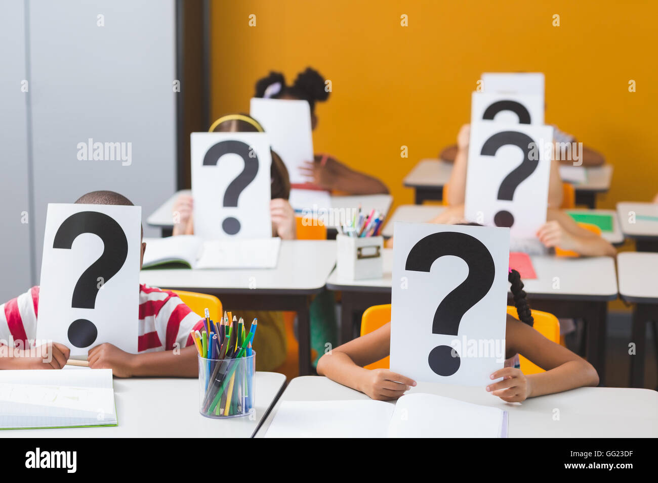 School kids covering their face with question mark sign - Stock Image