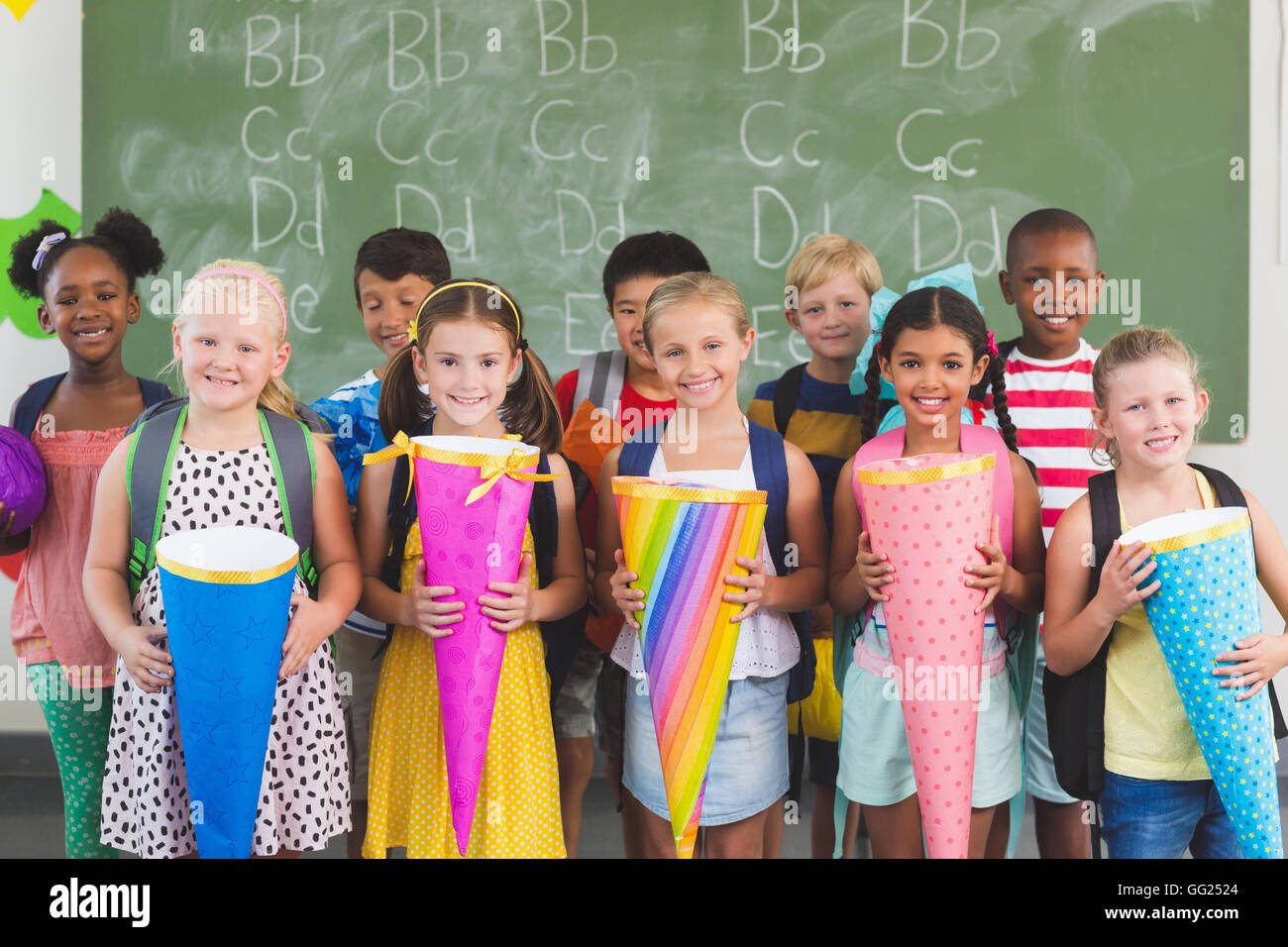 Happy kids holding gifts in classroom - Stock Image