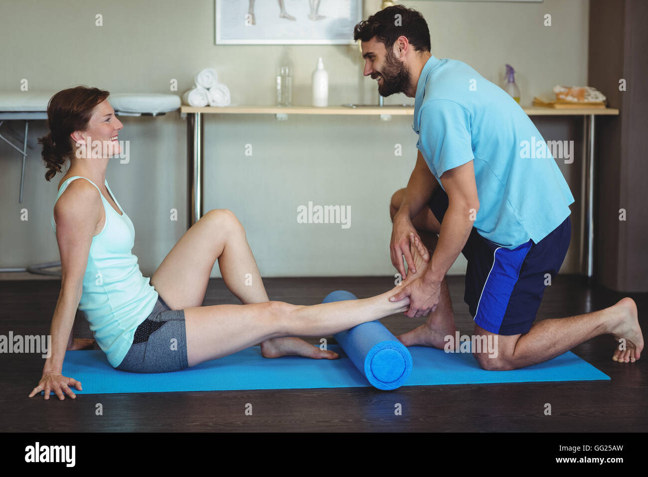 Physiotherapist doing leg therapy to a woman using foam roll - Stock Image