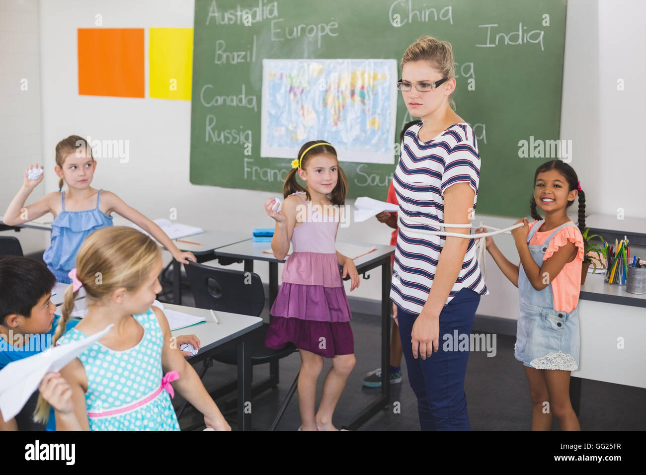 School kids tying up female teacher with rope in classroom - Stock Image