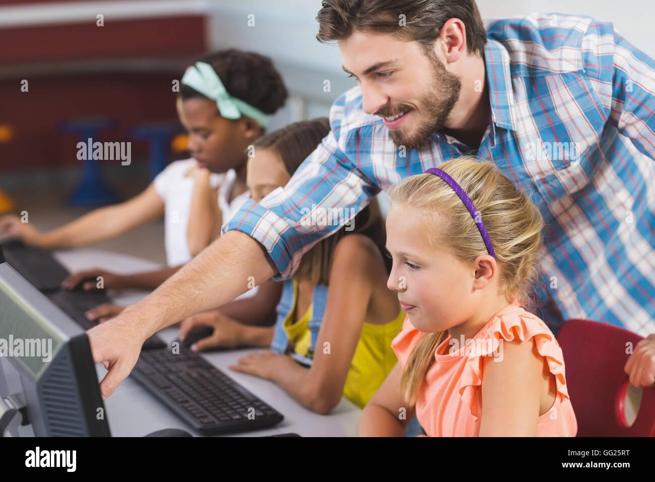 Teacher assisting schoolgirls in learning computer Stock Photo