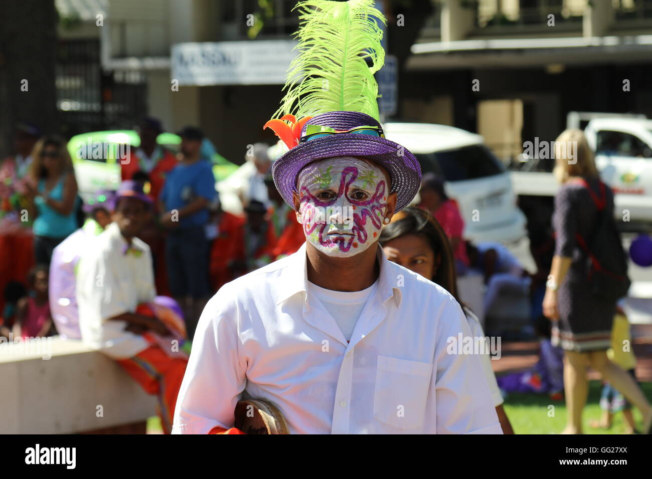 A man with face paint and a feathered hat at the 2016 Stellenbosch wine parade - Stock Image