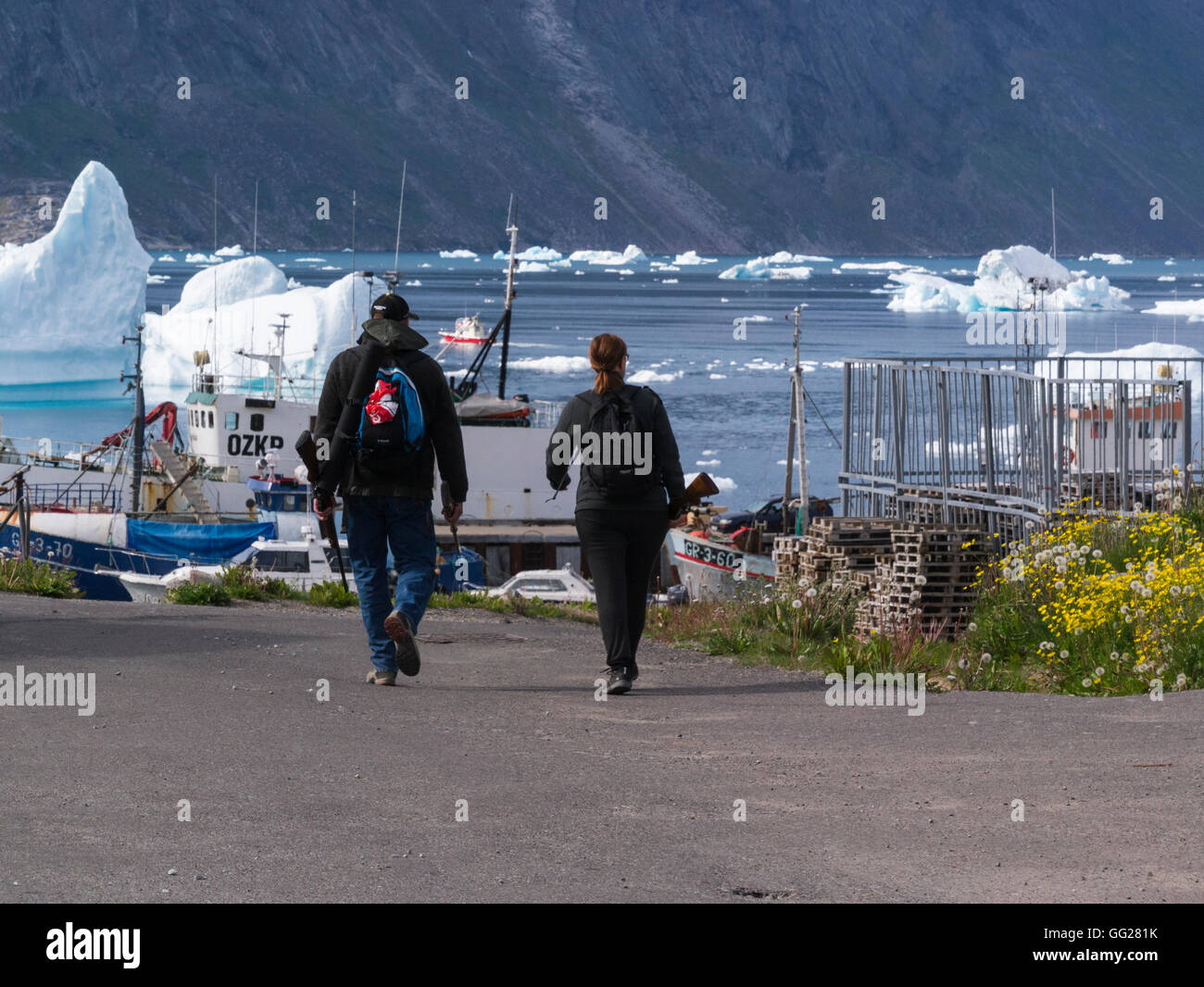 Man woman holding rifles going to hunt reindeer or seal Narsaq South  Greenland small fishing farming community Stock Photo
