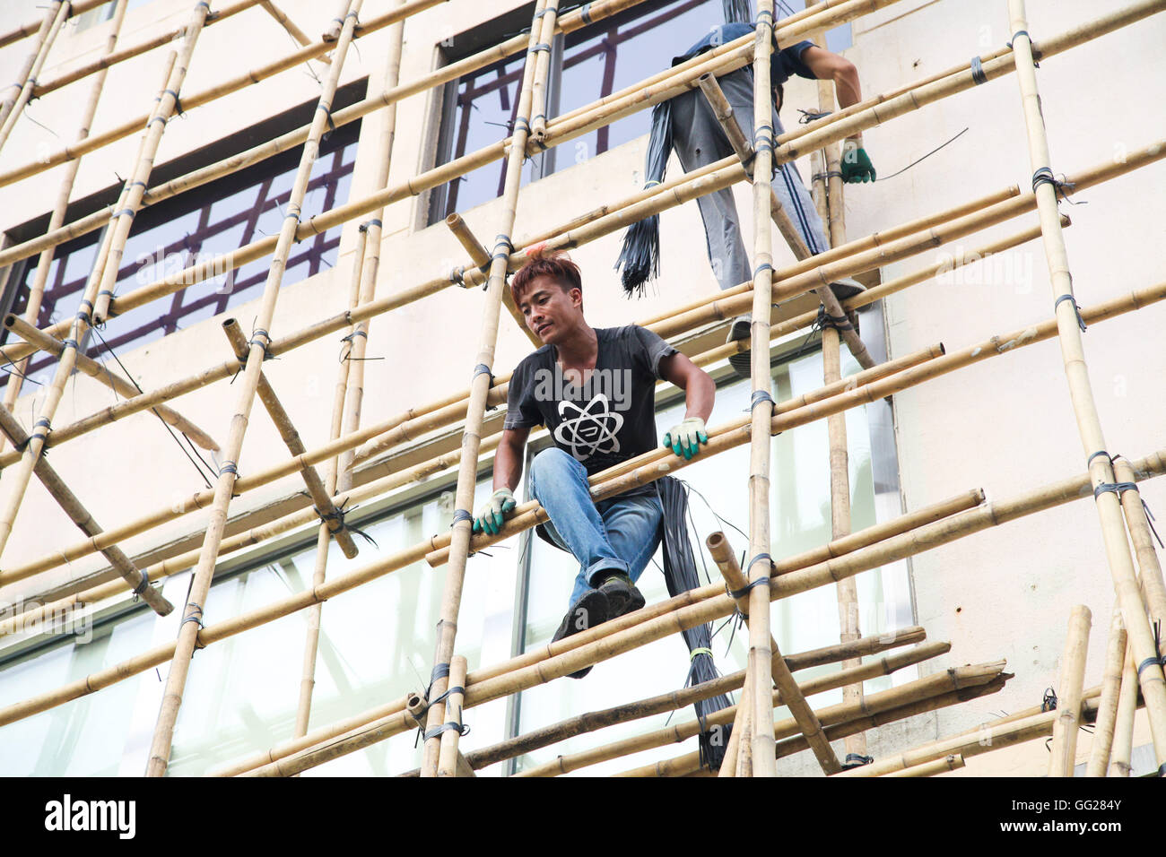 Chinese construction workers on bamboo scaffolding, Hong Kong, China - Stock Image