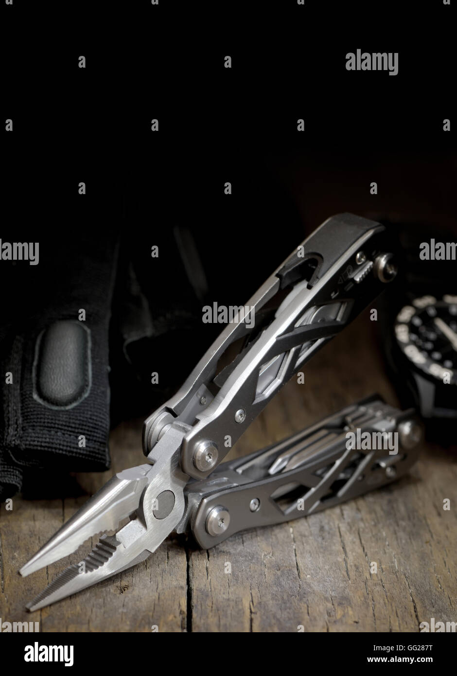 stainless steel multitool isolated on wooden table - Stock Image
