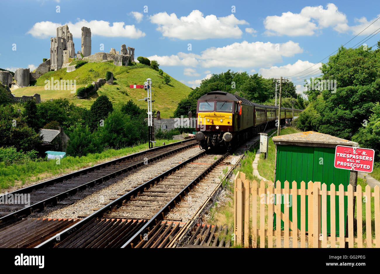 Corfe Castle beside the Swanage Railway. Seen from the platform as a special train approaches the station. - Stock Image