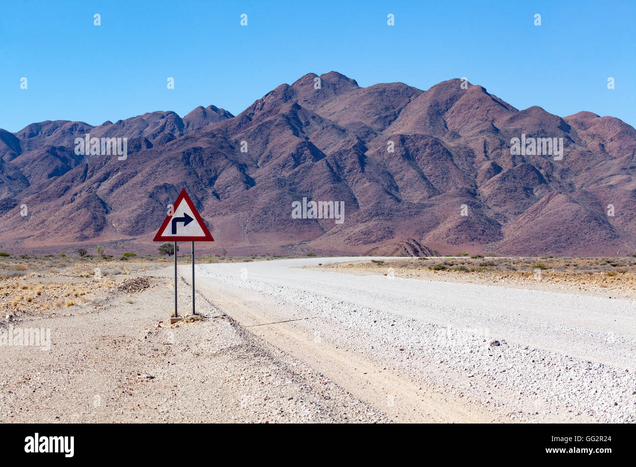 Namibia Right turn on a road in front of mountains. - Stock Image