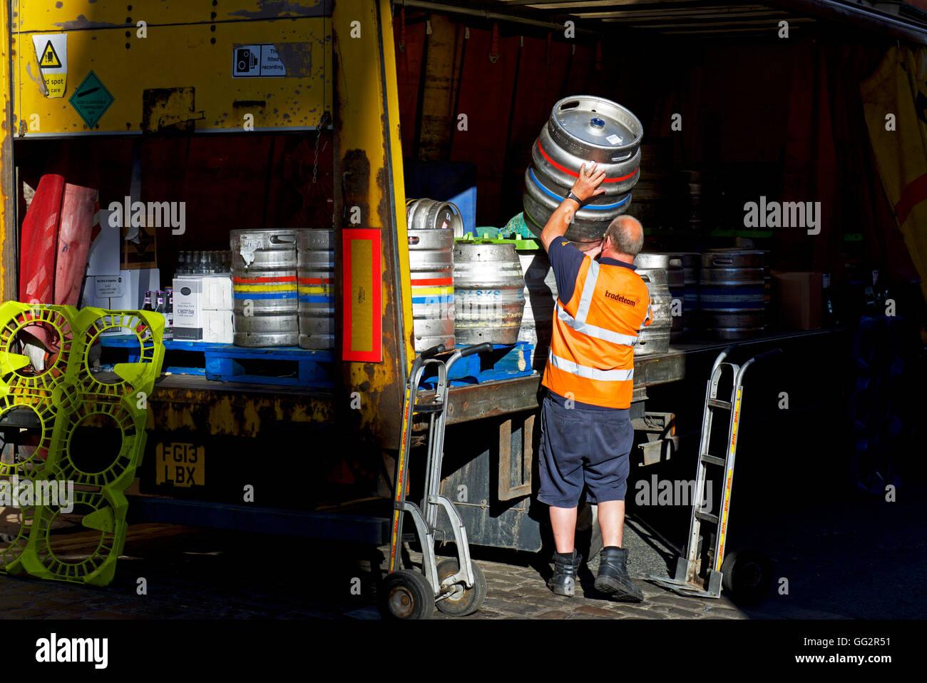 Man loading beer barrels onto lorry, York, North Yorkshire UK - Stock Image