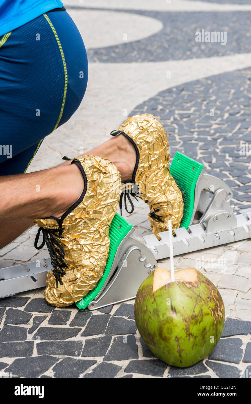 94394180eaf0c5 Brazilian athlete wearing flip flops crouching at the start position in running  blocks with a coco gelado coconut in Copacabana